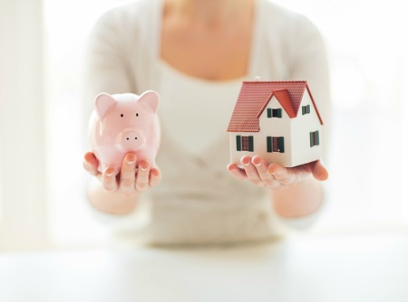 woman holding piggy bank and small house